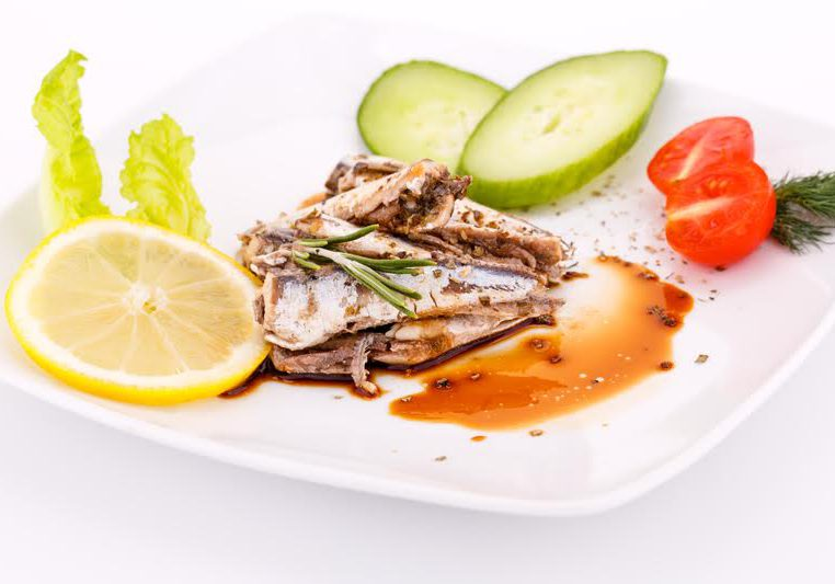 Fish, vegetables and lemon on white plate.