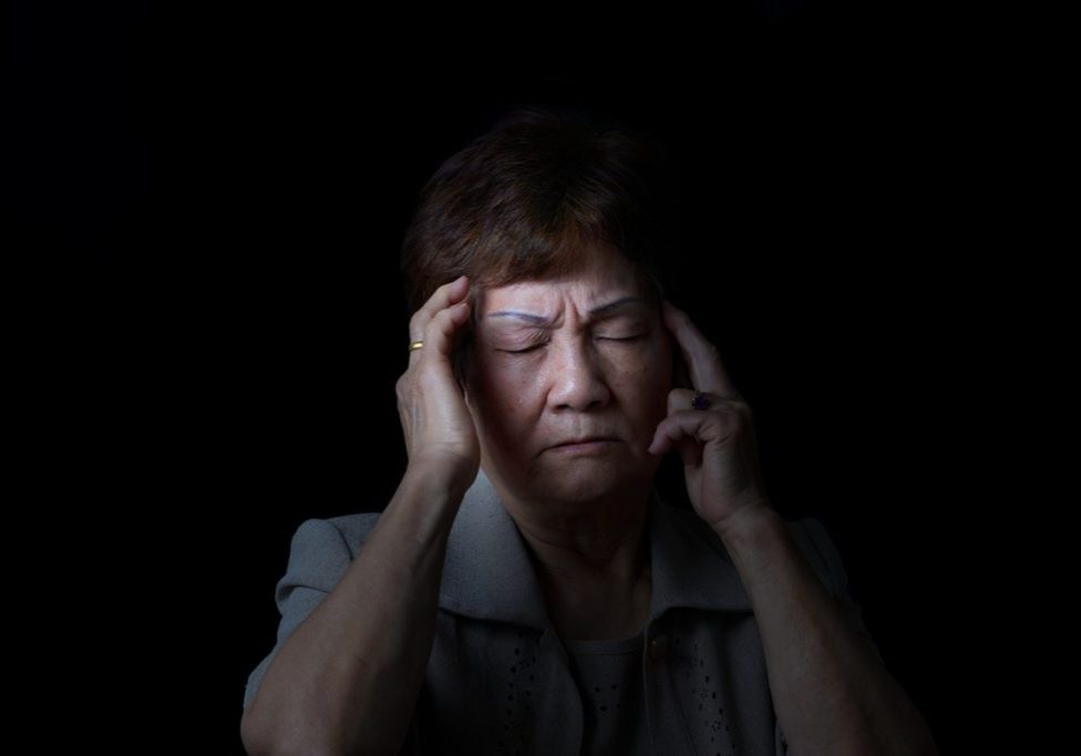 woman with headache who needs a chiropractic adjustment